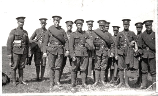 Group of soldiers in a field wearing Oliver gear & 5 Button Tunics